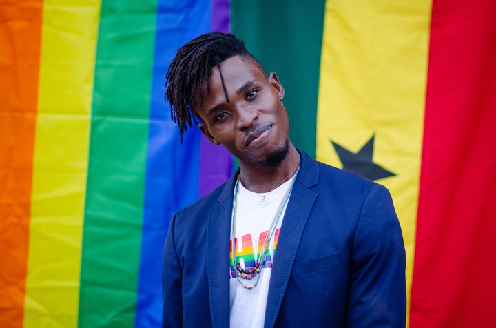 Alex Kofi Donkor vor der Regenbogenfahne