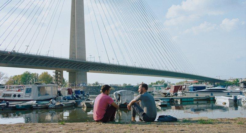 Zwei Menschen, die vor einem Fluss mit Booten sitzen
